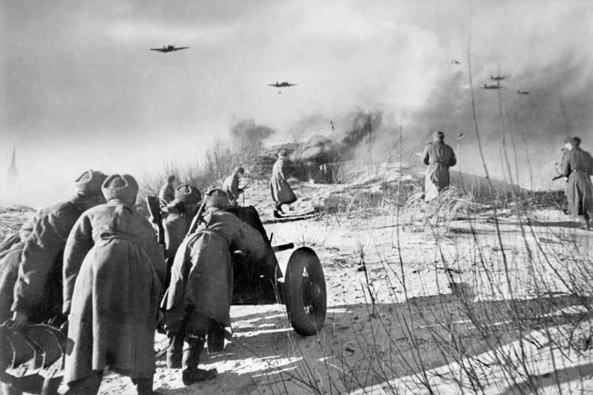 Red Army soldiers manhandle an artillery piece into position while comrades scramble forward across the sandy landscape near the East Prussian town of Tilsit on the Baltic Sea in October 1944. Soviet aircraft strike targets of opportunity in the distance.