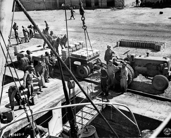 """At a French port along the English Channel, Army stevedores form a """"bucket brigade"""" to move empty five-gallon gas cans from a ship to a trailer."""