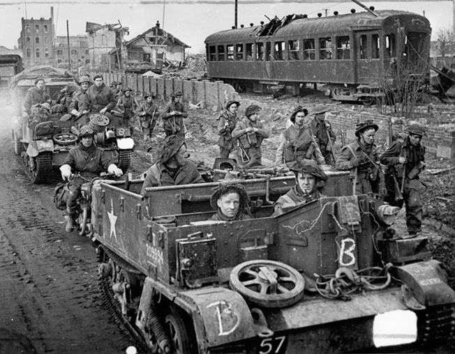 Gutted streetcars lie derelict along a rail siding as British soldiers, some walking and others aboard Bren Gun carriers, advance through the shattered streets of Goch on February 25, 1945, following the town's capture during Operation Veritable.