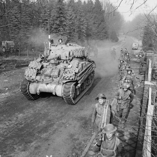 A Sherman tank rolls past soldiers of the British 43rd Wessex Division on February 17, 1945. This photograph was taken during the Allied advance on the German town of Goch as fighting raged in the Reichs- wald.