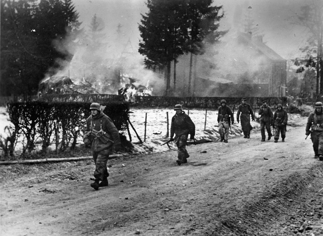 Photographed on the move prior to Operation Veritable, German panzergrenadiers move through a village as several buildings are consumed by flames. Battle-hardened German soldiers mounted effective defensive efforts in the Reichswald, delaying the movement of British forces deeper into the industrialized Ruhr.