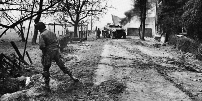 Paratroopers of the American 17th Airborne Division inspect the area and warily approach a German Sdkfz 251 half-track they knocked out minutes earlier. The vehicle still belches smoke after taking a direct hit from a bazooka on the morning of March 24, 1945.