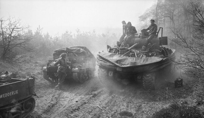 Giving a lift to a few infantrymen from the 6th Kings Own Scottish Borderers, a duplex drive (DD) Sherman tank rolls forward on March 25, 1944. The DD Shermans were designed to use drive systems that traversed both land and water, while a canvas shield was raised to assist with buoyancy.