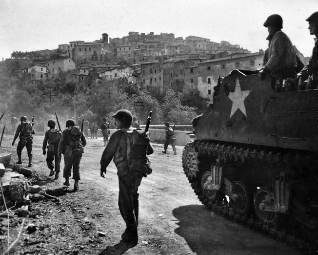 """A self-propelled M7 """"Priest"""" assault weapon mounting a 105mm howitzer pauses along a road near the town of Cori, south of Rome, as American soldiers stream past toward the Eternal City."""
