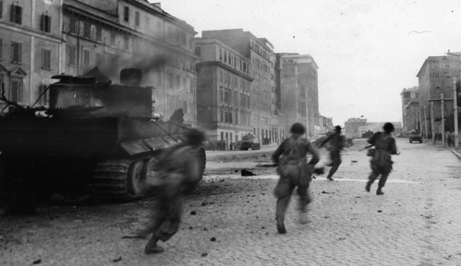 American soldiers, among the first Allied troops to enter Rome, sprint past a burning German tank to take up positions along a city street. An American tank, providing fire support as the infantrymen clear houses, is seen in the distance at right.