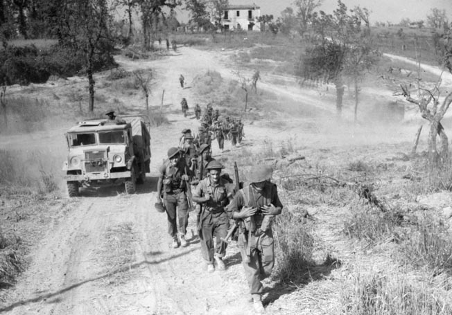 Canadian troops march along a dirt road toward new positions in the valley of the Liri River.