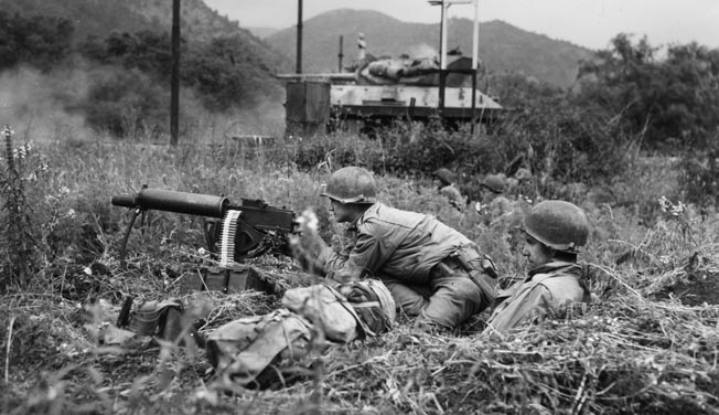 An American M10, open-turreted tank destroyer has opened fire on a German position at the Galleria di Mont Orso tunnel, where two enemy battalions have been trapped inside. An American soldier is ready to fire his .30-caliber machine gun if the Germans emerge to fight.