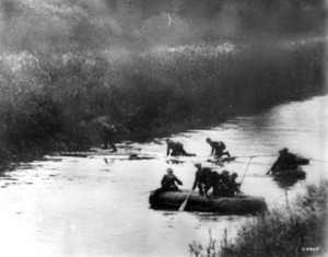"""Soldiers of the 7th Panzer """"Ghost"""" Division paddle across the Meuse River, while others scamper over a thin bridge."""