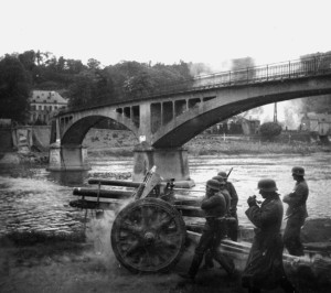 The 7th Panzer Division artillery opens up on French positions near a destroyed bridge.