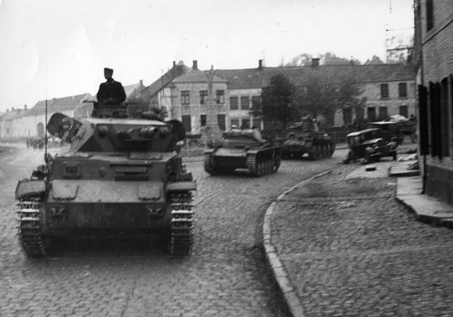 Panzer IVs and a T(38) roll through another small French town.