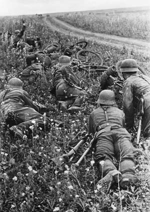 German infantrymen pause and take cover as the reports of Soviet firearms are audible in the distance. This image was captured during the German drive toward Rostov on the River Don in 1941.
