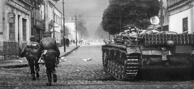German soldiers fighting in the streets of of Rostov advance warily alongside a self-propelled gun that is being used to root out snipers and eliminate Soviet strongpoints during close-quarter urban combat.
