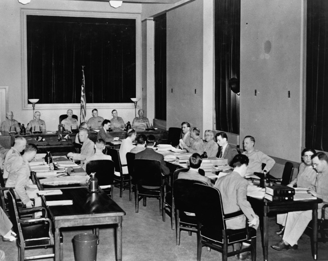 At the Department of Justice in Washington, D.C., Room 5235 was converted into a courtroom for the trial of the Operation Pastorius conspirators. The generals of the military commission that presided are in the rear, while Attorney General Francis Biddle and the Prosecution staff are on the right and defense attorneys are on the left. Behind them are the defendants.