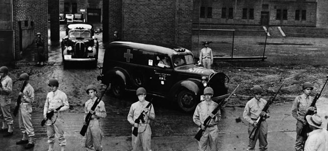 ca. 1942, USA --- Armed soldiers guard the ambulances that are carrying the bodies of six executed Nazi saboteurs who plotted against the United States away from Washington jail. --- Image by © Hulton-Deutsch Collection/CORBIS