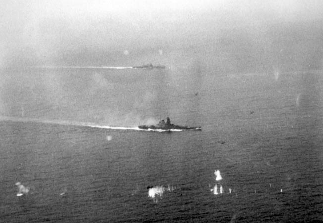 The Japanese super battleship Yamato, with 18.1-inch main guns, stirs a wake as it maneuvers during the battle off Samar. A Japanese heavy cruiser is visible of the Yamato's port quarter.