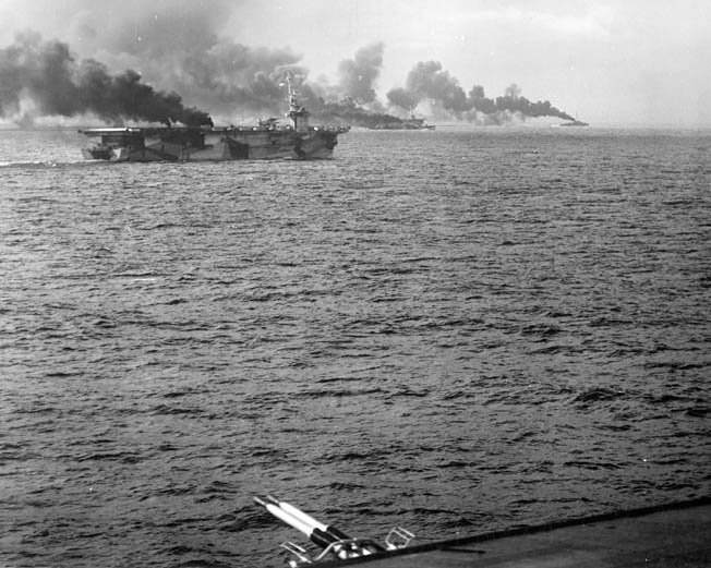 During the opening minutes of the Battle off Samar, the escort carrier USS Gambier Bay and others make smoke to disrupt the aim of Japanese gunners aboard the heavy cruisers and battleships that were poised to wreak havoc with the American troops and transports at Leyte.