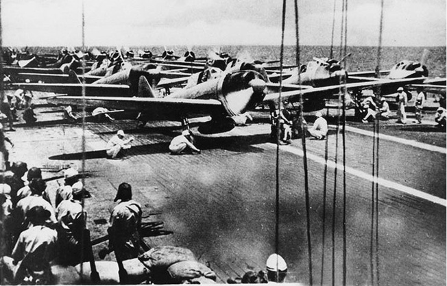 "Engines roaring, Japanese Aichi ""Val"" dive-bombers and Mitsubishi Zero fighters await the signal for takeoff from the deck of the aircraft carrier Shokaku during the Battle of the Santa Cruz Islands on October 26, 1942."