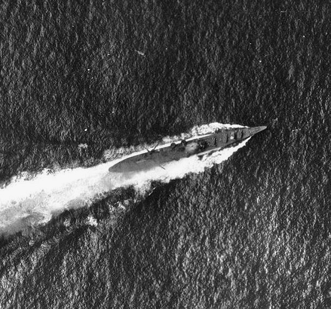 Under attack by American dive-bombers, the Japanese cruiser Chikuma maneuvers violently on October 26, 1942. Damage and a plume of smoke from the impact of a 1,000-pound bomb are faintly visible amidship.