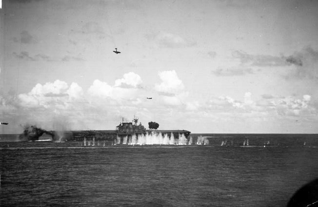 Geysers from antiaircraft shells churn the water surrounding the USS Hornet as Japanese torpedo- and Dive-bombers attempt coordinated attacks on the American warship.