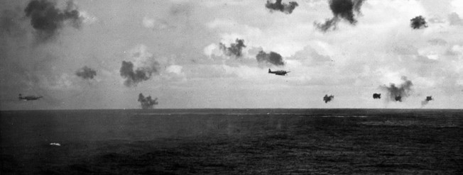 A U.S. Navy combat photographer aboard the cruiser Pensacola captured this image of Japanese torpedo bombers attacking the aircraft carrier Hornet. Although her escorts and combat air patrol resisted valiantly, Hornet was lost.