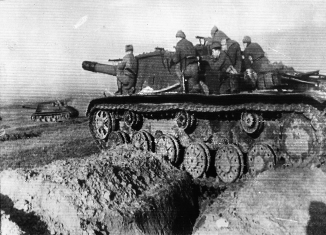 Less than 100 miles east of Berlin, Soviet tanks race through a breach in the German lines. Infantrymen often rode atop the tanks to advance more rapidly and provide support for the armor during combat.