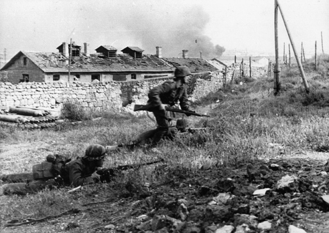 A German soldier exposes himself to Soviet gunfire as he attempts to push forward. His comrades continue to lie low behind the limited cover of a small embankment.