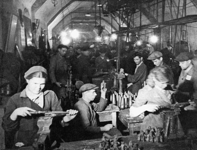 Toiling away in an underground shelter lit by bare lightbulbs, citizens of Sevastopol work overtime to aid the defense effort.
