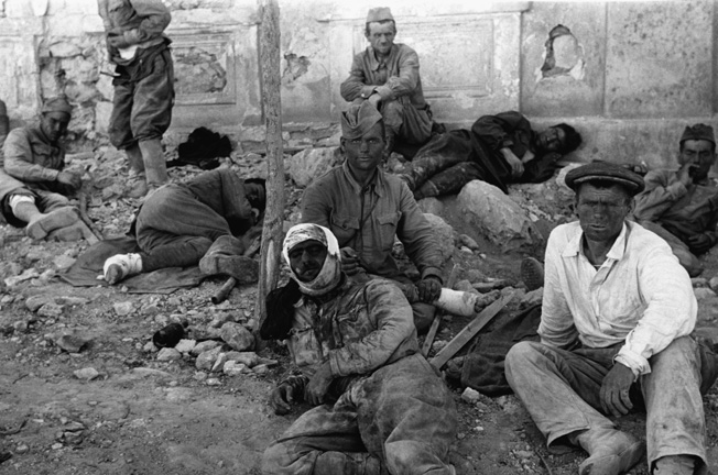 A group of Russian soldiers rests on a pile of rubble in the ruined streets of Stevastopol after a difficult but successful battle. August 1942 Sevastopol, Russia.