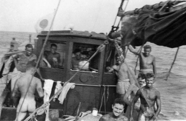 As the Krait sails toward Singapore harbor, members of the Australian raiding party are busily stain- ing their bodies in preparation for the raid. At a distance the raiders' stained bodies resembled the native pop- ulation more closely.