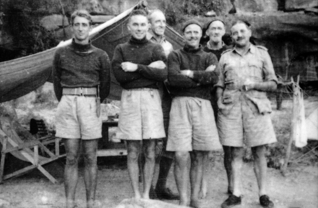 """Six members of the Z Unit team pose for a photographer outside a tent at their training camp: Major Ivan Lyon stands second from left; J.P McDowell is second from right; Major J.A. """"Jock"""" Campbell is at far right."""