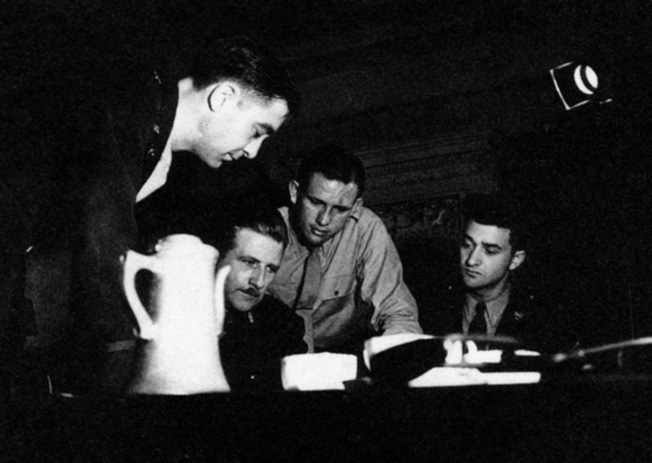 Before parachuting into occupied France, an OSS Jedburgh team is briefed on numerous topics. Agent John K. Singlaub is shwon second from the right.