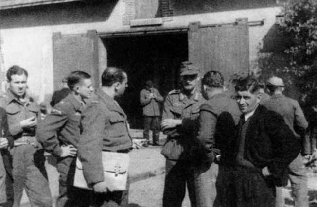 OSS operatives interrogate a German prisoner recently captured by French partisans known as Maquis. John Singlaub is at the left with his hand on his hip.