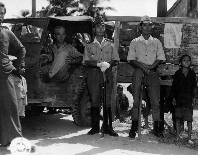 American Lieutenant Frank G. Beiser and two officers belonging to the Japanese Marine contingent on the Island of Hainan pose for the camera beside a sign proclaiming the end of the war and urging any escaped Allied prisoners to come in from hiding.