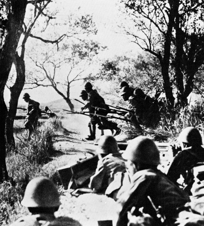 Japanese troops leap from the safety of a trench line and advance against British positions as a machine-gun crew prepares to fire in support of the charge. Such attacks, while heroic, were often repulsed with severe losses.