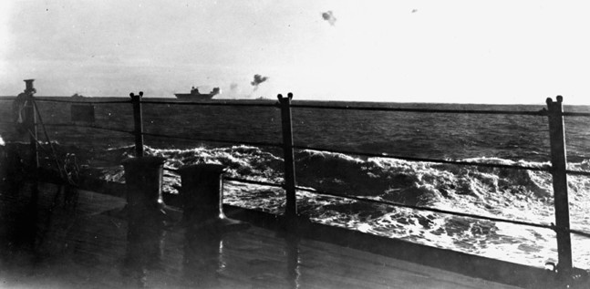 In this photograph taken from the deck of the cruiser USS Portland, smoke billows from the Enterprise which has just taken a hit from a Japanese bomb.