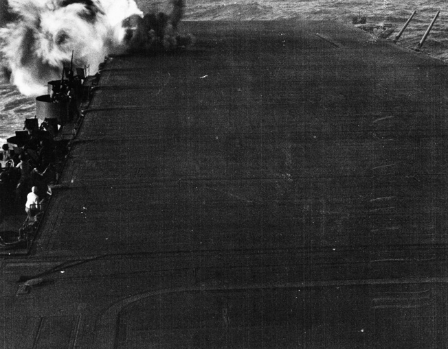 Smoke pours from the impact site of the second of three bombs to strike the carrier Enterprise during the Battle of the Eastern Solomons. This one hit the starboard side of the flight deck aft.