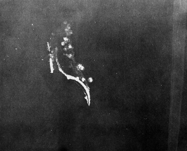 As two Japanese destroyers maneuver violently to evade American bombs, the carrier Ryujo lies dead in the water. Ryujo later went to the bottom.