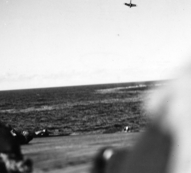 Blasted by U.S. Navy antiaircraft fire, a Japanese plane crashes into the sea off the port bow of the Enterprise.