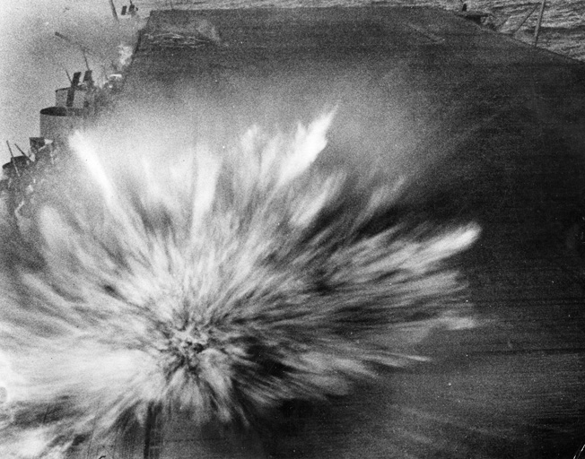 On the afternoon of August 24, 1942, a third bomb penetrates the flight deck of the USS Enterprise and explodes. In this spectacular image, the moment of detonation is captured. Unfortunately, the combat photographer Robert Frederick Read was killed during the battle.