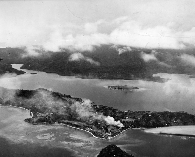 Following a U.S. air raid on Japanese positions on Tulagi, August 7, 1942, smoke billows from the island's cricket grounds.