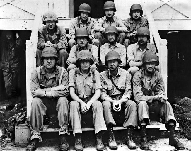 Officers of the U.S. Marine Corps and the U.S. Navy who held command responsibilities at Tulagi posed for this photograph after the island was secured. On the front row left to right are Lt. Col. O.K. Pressley, Colonel Merritt A. Edson, Lt. Col. H.E. Rosecrans, and Lt. Col. R.E. Hill. The middle row left to right includes Navy Lieutenant E.B. McLarney, Brig Gen. W.H. Rupertus, Colonel R.C. Kilmartin, and Major William Enright. On the back row left to right are Captain Ralph Powell, Captain Daryle Seeley, and Captain Thomas Philpott.