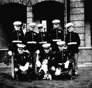 U.S. Marins of Company B, 4th Regiment pose proudly with their mascot, the indomitable Soochow. A uniform was specially made for the famous canine.