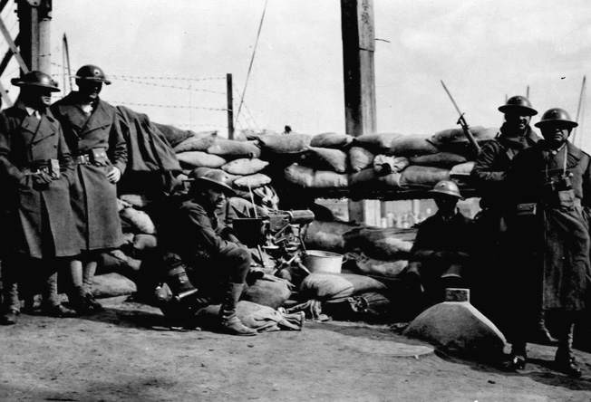 During a pause in the frenzied flight of Chinese refugees from fighting between the Japanese and Allied forces, U.S. Marines take cover behind a barricade of sandbags and man a machine gun near a bridge across Soochow Creek.