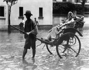 High and dry for a moment, a U.S. Marine rides through the floodwaters along a street in Shanghai sometime in 1937.