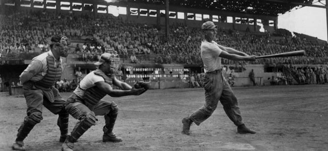 """Former professional baseball player """"Catcher"""" Batcha takes a swing at a pitch while playing in a game at Riza Stadium near Manila, Philippines. This photo was taken shortly after the liberation of the city from Japanese occupation, and several other former major league players participated in the game."""