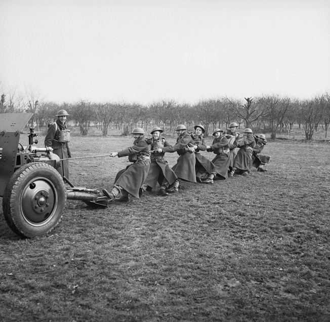 The players of the British Bolton Wanderers football club enlisted in the 53rd Field Regiment of the British Army. In this publicity photo, team members pull an artillery piece into position on a firing range.