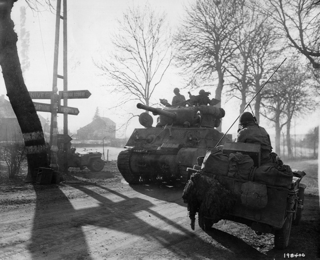A Sherman tank of the 9th Armored Division heads into action against the advancing Germans during the Battle of the Bulge.