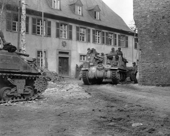 Tanks of the 9th Armored Division roll through an abandoned French village.