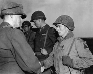 For heroism in action at St. Vith, Technical Sergeant Michael Chincher of the 9th Armored Division receives the Distinguished Service Cross from Maj. Gen. John W. Leonard, the division commander, on April 11, 1945.