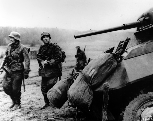 German soldiers move past an abandoned U.S. armored vehicle during the early hours of the Battle of the Bulge.
